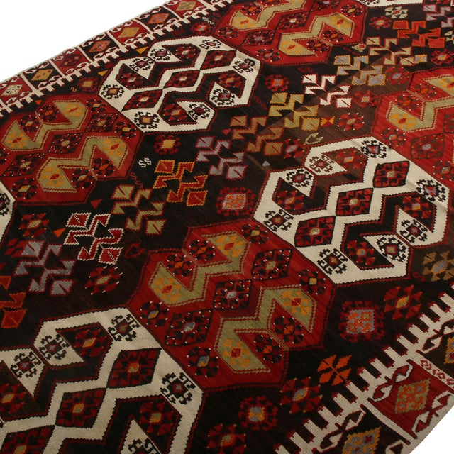 Flat woven in Turkey originating between 1950-1960, this vintage mid-century geometric kilim hails from the city of...