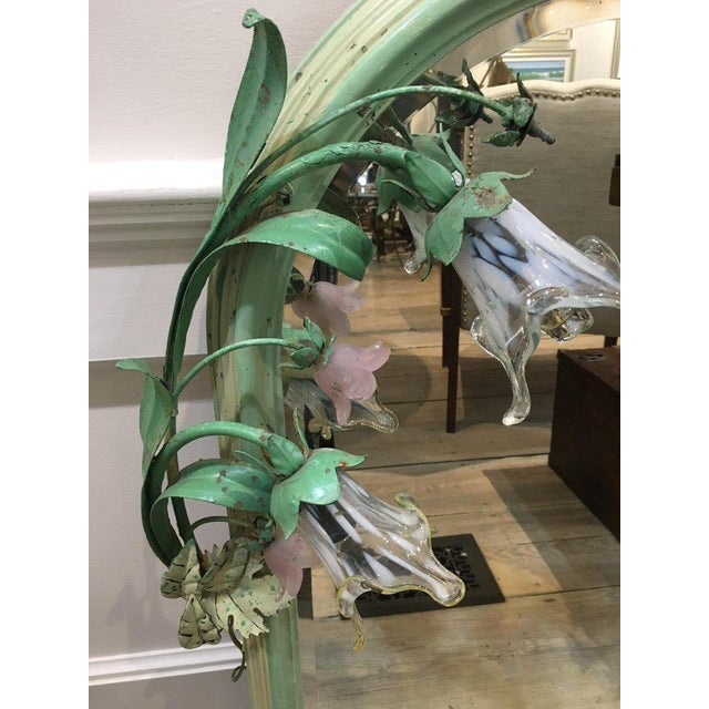 A wood frame mirror with the original green paint with painted iron flower stems with glass flowers, two of which light...