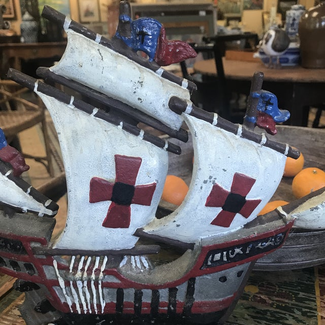 Vintage iron ship doorstop with cross sails in white, reds, and blues.