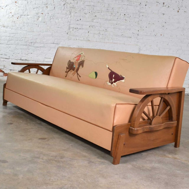 Fabulous mid-century cowboy western wagon wheel convertible sofa reminiscent of a 1950s dude ranch. It is in wonderful...