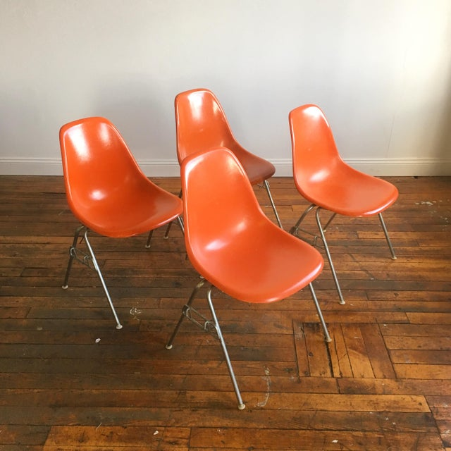 Set of 4 vintage Eames for Herman Miller molded fiberglass shell chairs on stacking bases in Red Orange. CONDITION: Very...