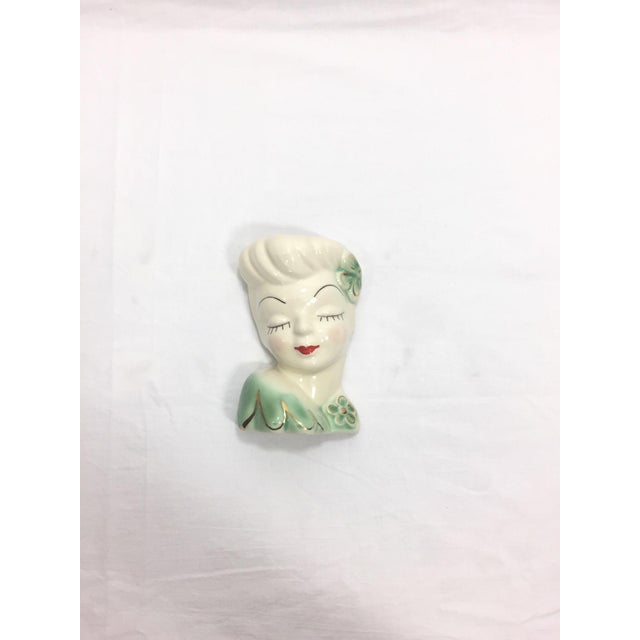This is a lovely 1950s hand painted Glamour Girl wall pocket or head vase. She has green and gold accents with black...