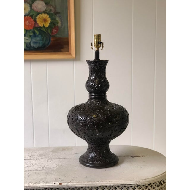 20th Century lamp cast from plaster into an urn shape with a relief of a classic western oak leaf and floral pattern. The...