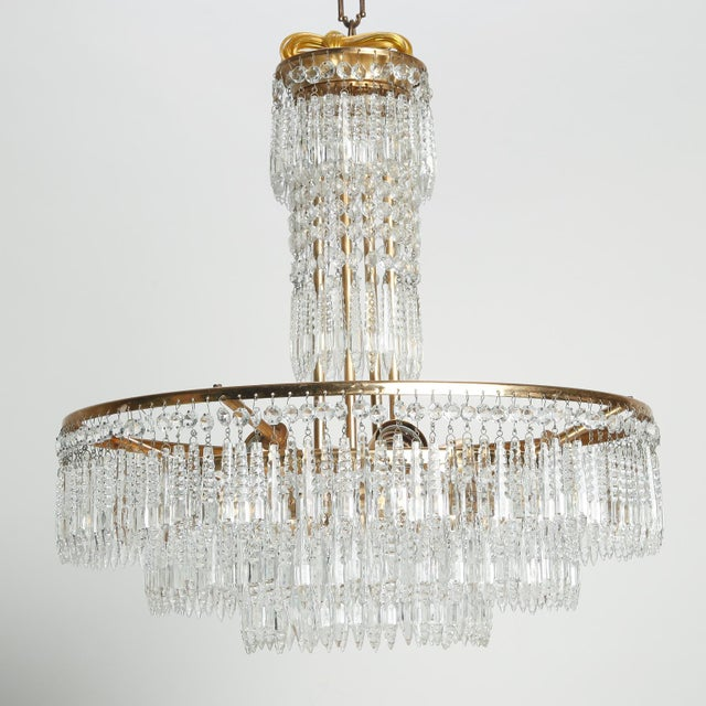 Circa 1920s French chandelier features a brass frame with narrow center support decorated with crystal pendants and three...
