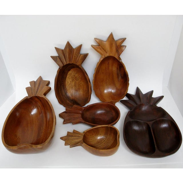 A collection of assorted carved wood bowls with pineapple motif. The set contains bowls in different shapes and sizes. No...