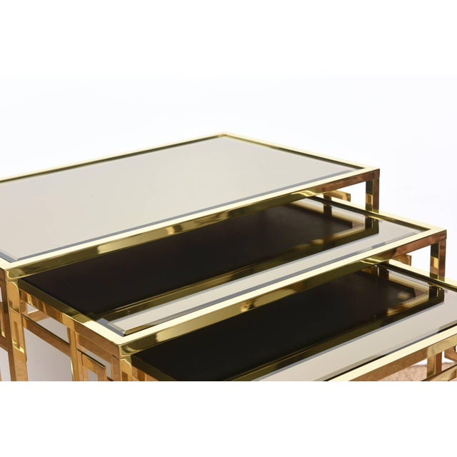 These set of 3 Italian greek key nesting tables are polished brass with original mirrored bronze glass tops. They were...