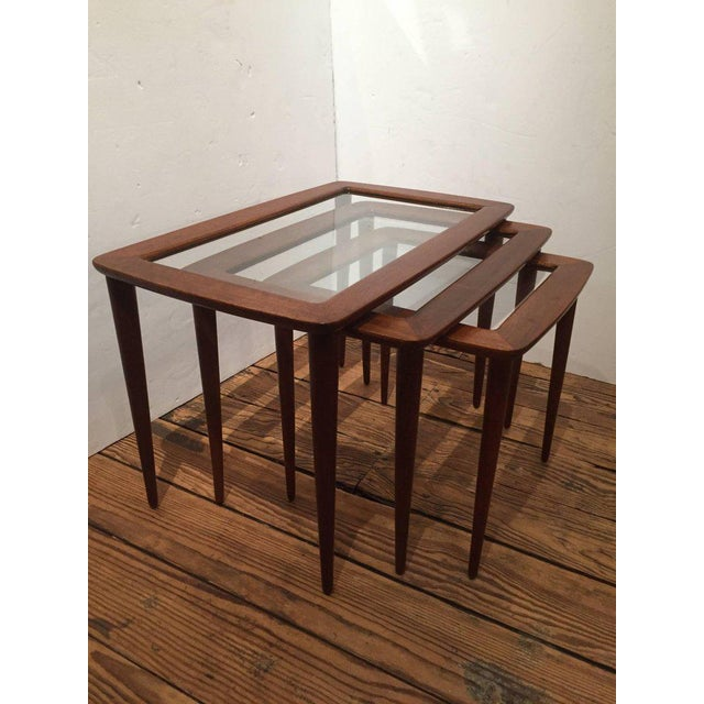 Rare set of sleek Italian nesting tables in graduated sizes as listed below, having lustrous teak wood frames and glass...