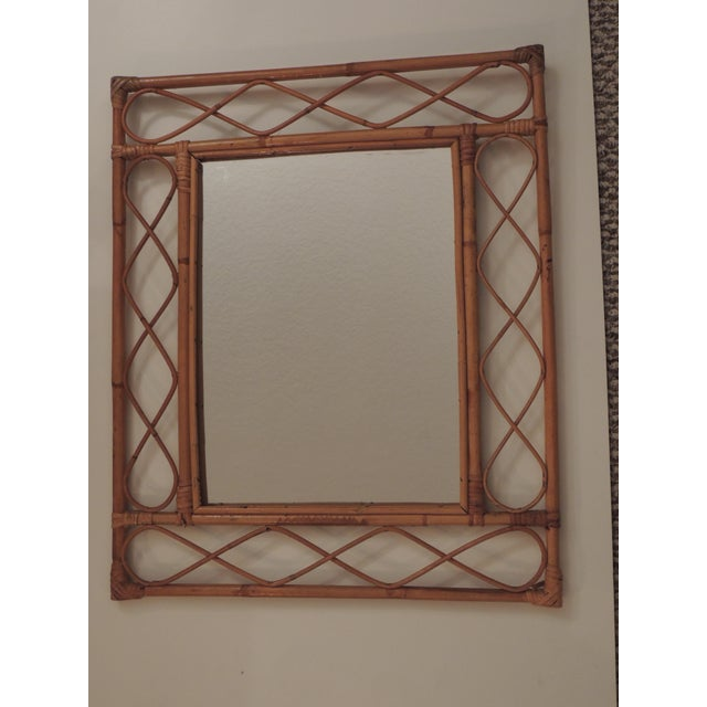Vintage bamboo and rattan wall mirror. Rectangular and undulating trellis design. Original hanging hooks on top. Size:...