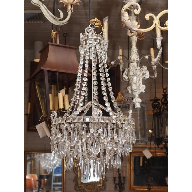 A Louis XVI style crystal chandelier. Light emerges from 3 inside metal cups for the lightbulbs. Crystal swags holding a...