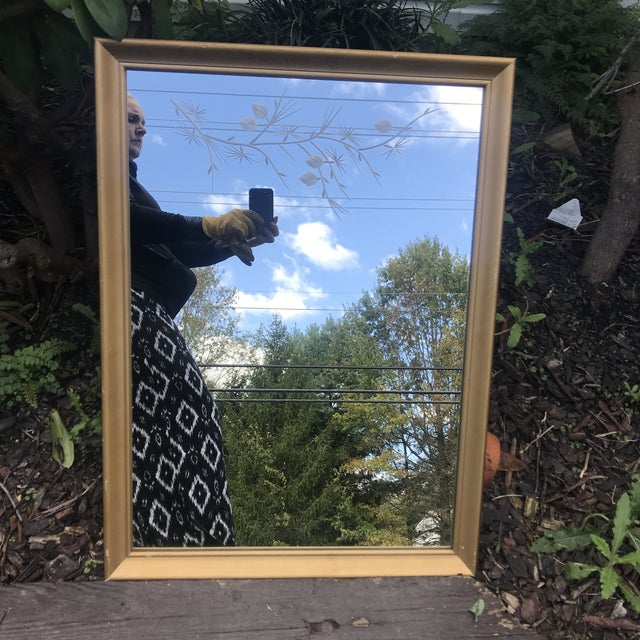 This gold paint-over-wood framed mid-century modern mirror boasts the prettiest etching of all! At the top of the mirror a...