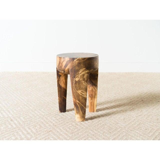 Mango wood stool with burnt finish and tripod base.