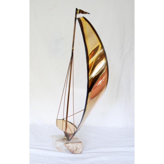 Graceful lines on this vintage torch cut metal sailboat. Sits on a rough cut piece of onyx. In the style of Curtis Jere.