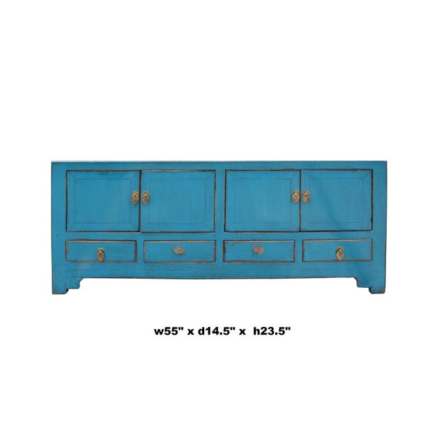 This is a low console TV stand cabinet with oriental hardware accent and different storage sections. The surface is...