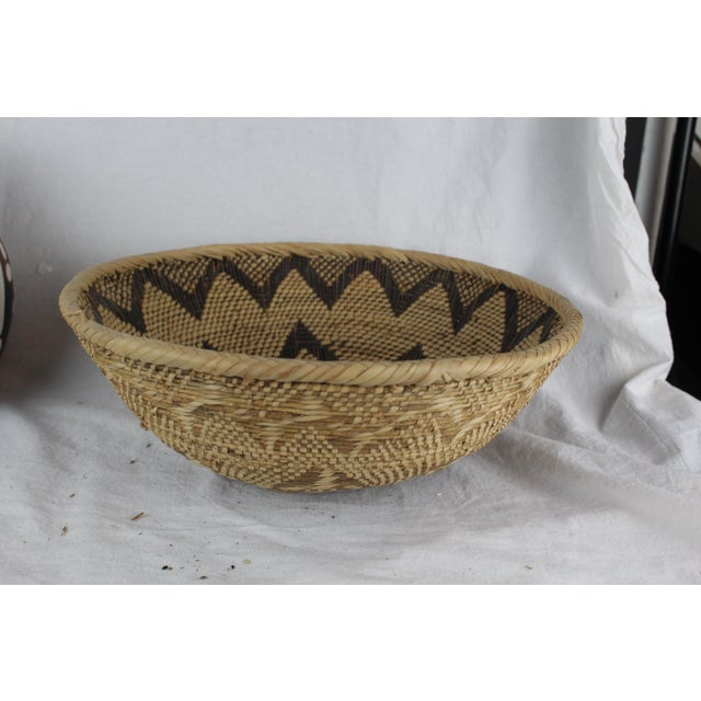 Handwoven grass African tribal basket in floral pattern with varying shades of brown and tan. Made in the mid 20th century.