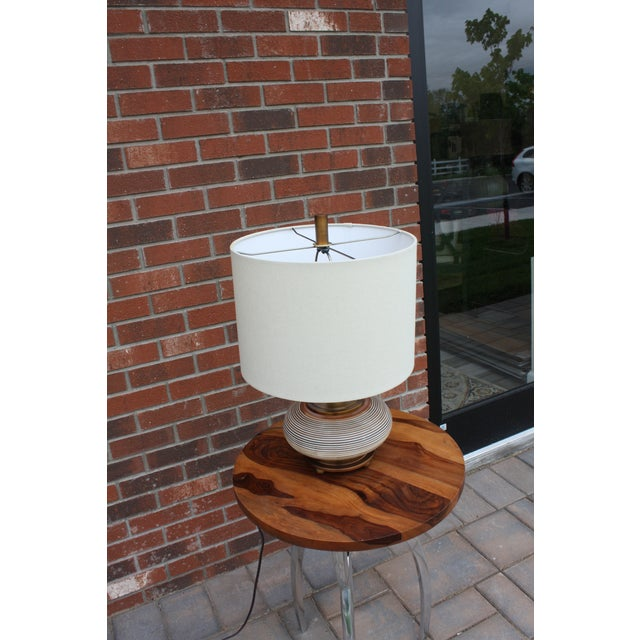 Adorable bronze lamp with horizontal white line base and off white fabric shade. Made in the 2010s in the style of boho chic.