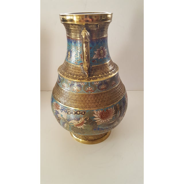 This Vase is a Japanese Treasure. Made of Brass and Delicate Hand painted Flowers Which Adorn the Body of The Vase. The...