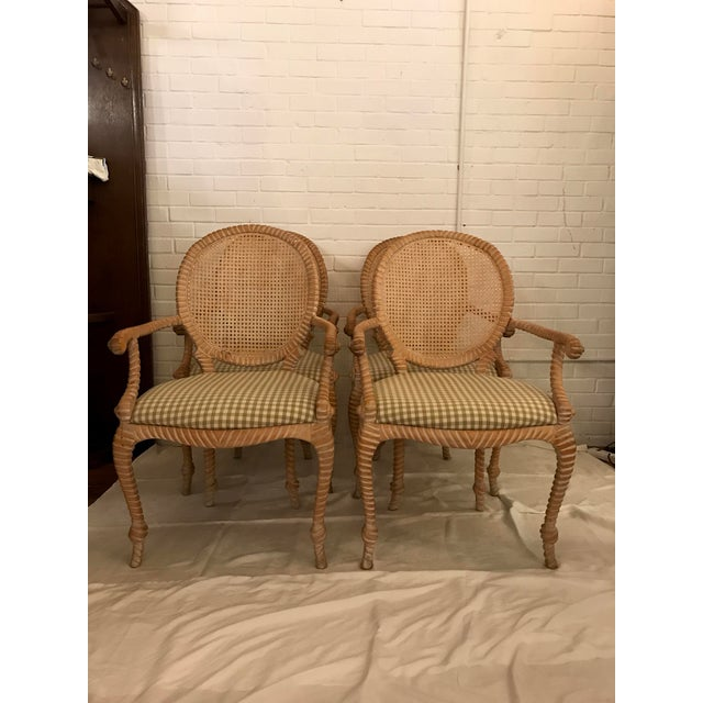 Set of 4 chairs arm chairs with carved rope and tassel design and caned backs. Designed and manufactured by Andre...