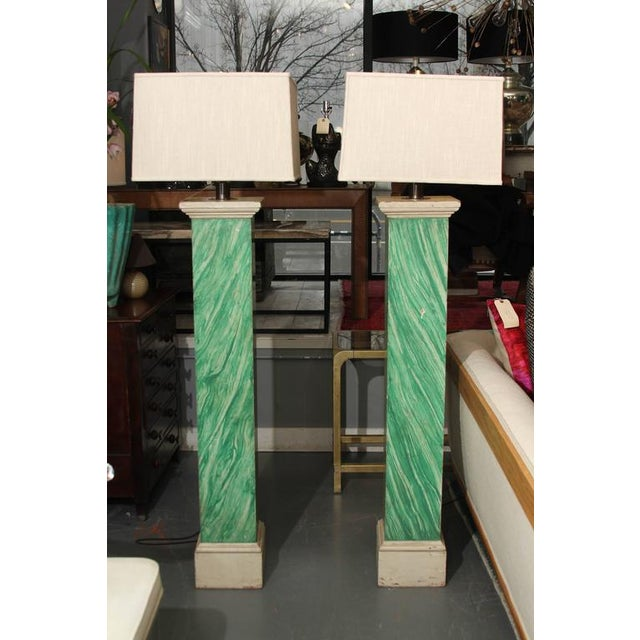 Pair of 1910 wood columns faux painted malachite wired as floor lamps. Measures: columns are 8 1/2 x 8 1/2 in at base....