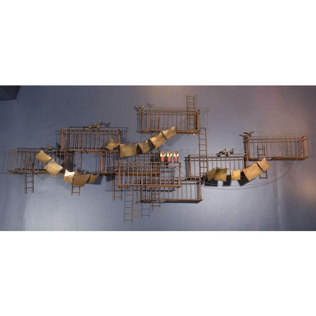 A vintage monumental abstract style wall sculpture of a New York City fire escape scene with pigeons, flower pots, and...