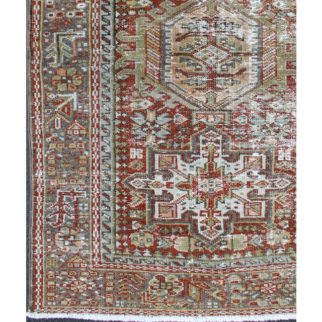 This early 20th century, handwoven Semi Antique Karadjeh rug features a red-colored field imbued with three large tribal...