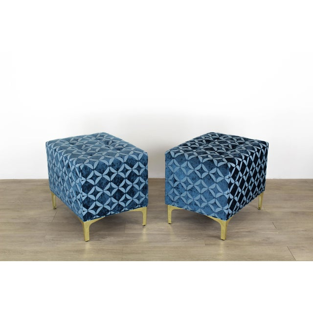 Elegant pair of custom design ottomans upholstered in a soft blue brocade chenille fabric and supported by elegant Italian...