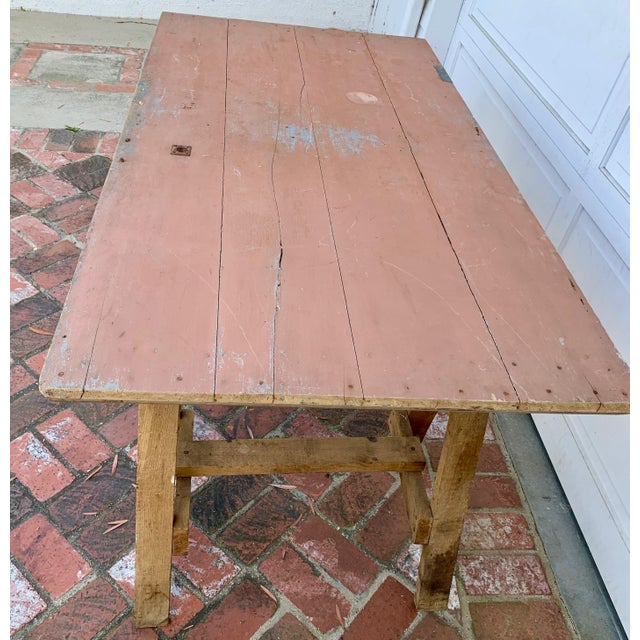 19th century French rustic pine country farmhouse table on two saw horse legs. This oak table on pine trestles has a...