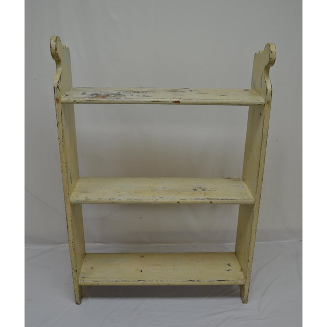 A sturdy three shelf pine unit with a sphinx-like curve to the top of the thick sides. The top and bottom shelves are...