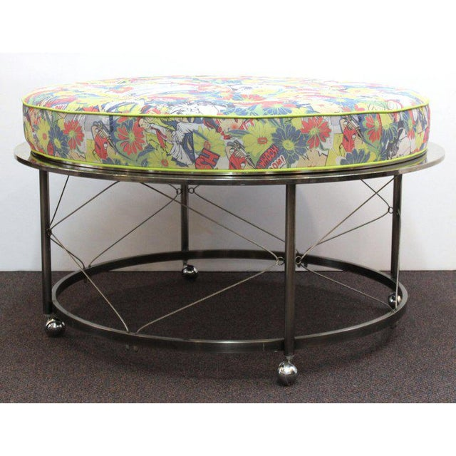 Mid century ottoman with chrome frame on castors and new upholstery. Features include a circular frame with wire trestles...
