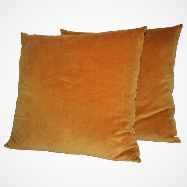 Pair of sunrise orange velvet pillows with linen backing, down and feather insert and zipper closure. Two pairs available.