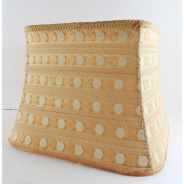 Creamy gold lacey dots with raw silk lining square lampshade. With a slight bell and rounded corners, fabric is a lacey...