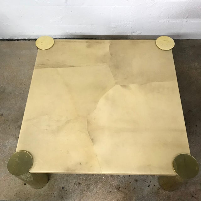 Coffee or cocktail table rendered in a top of lacquered Goatskin with cylindrical brass-plated aluminum legs designed by...