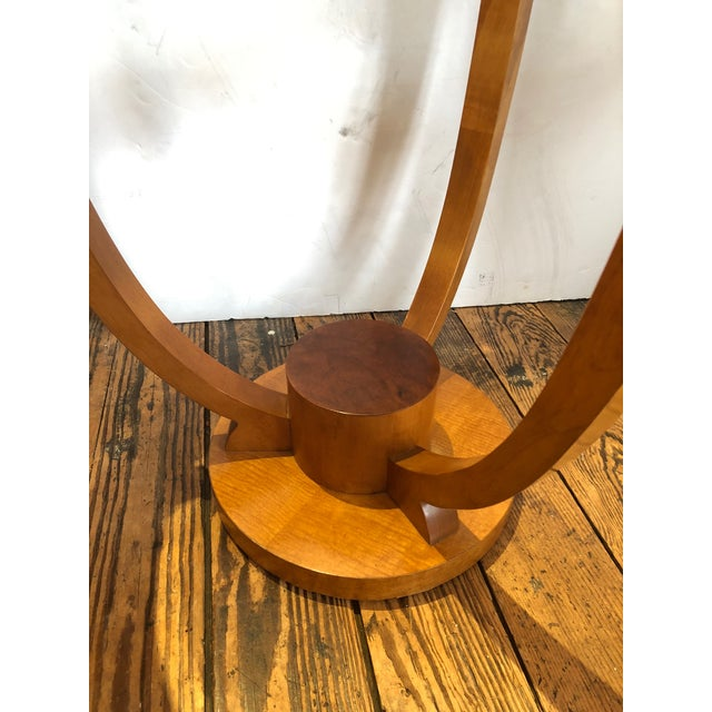 Lovely art deco style round end table, a pair is available, having blonde colored high gloss wood with black decorative...