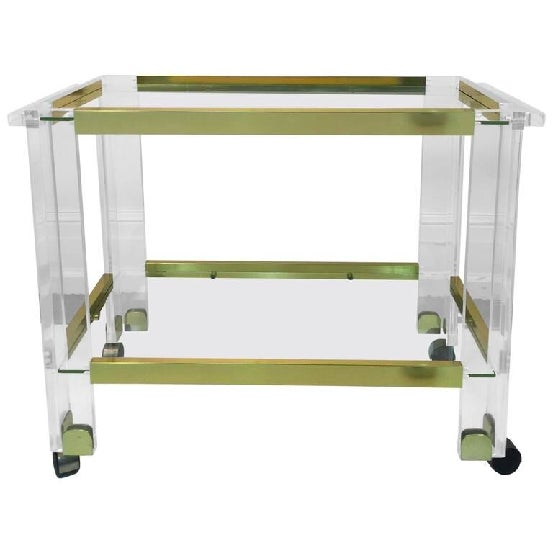 A stunning brass and Lucite two-tier bar cart by Charles Hollis Jones, circa 1970. Good condition with age appropriate wear.