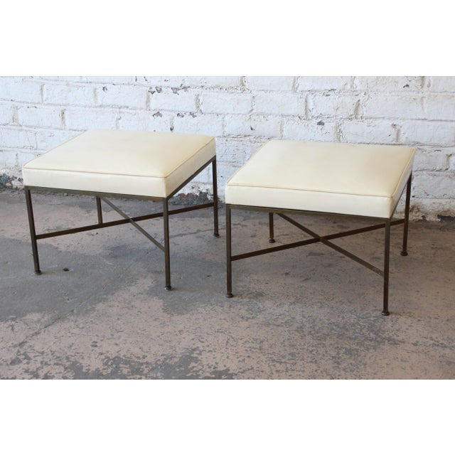 Offering a very nice pair of brass X-base stools or ottomans with upholstered seats designed by Paul McCobb for...