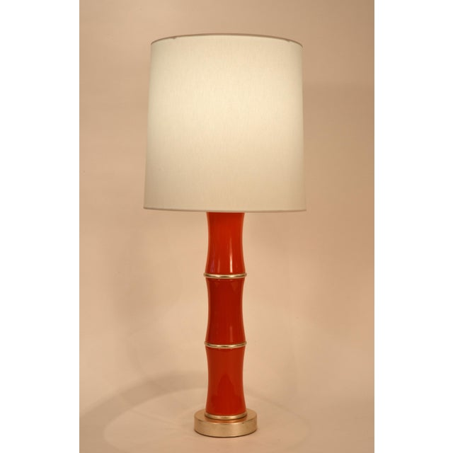 Pair orange porcelain task or table lamp with gold leaf wood base. Each lamp is in excellent condition, rewired for US...