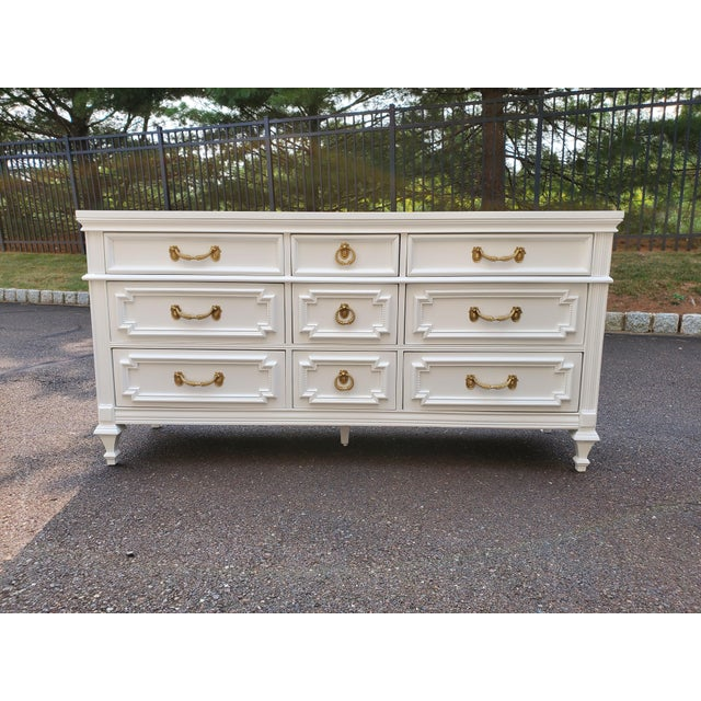 This is a vintage dresser painted glossy white. The hardware is gold. The drawers slide smoothly. This is Not distressed....