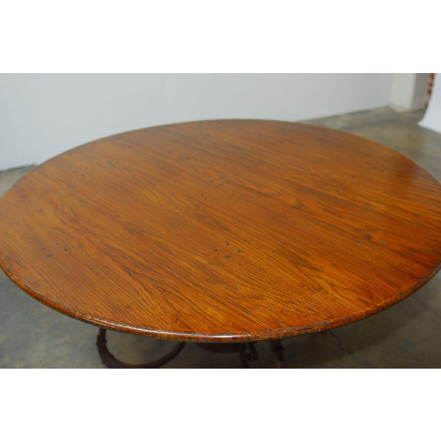 Impressive Italian round dining table made of reclaimed oak and supported by a wrought iron base featuring decorative...