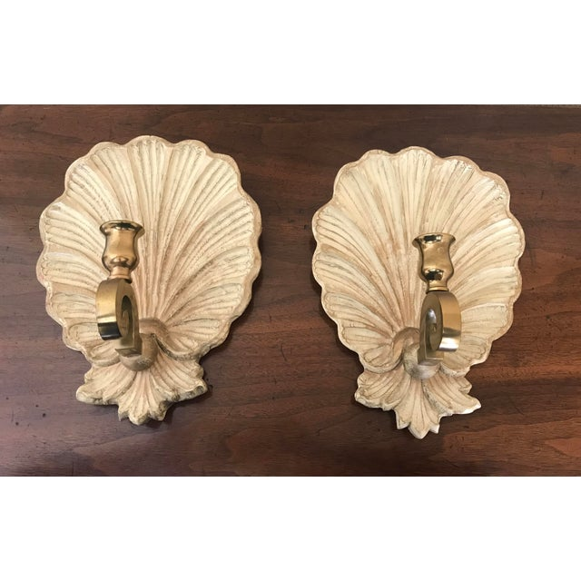 Beautiful pair of carved wooden shell candlestick wall sconces. The carved shell back is painted in a light cream color...