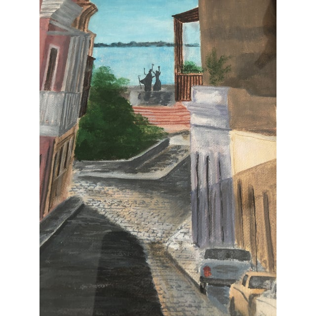 Signed Gavela and dated 1984 in lower right corner. Artwork depicts street scene with view of the water. On board, set...