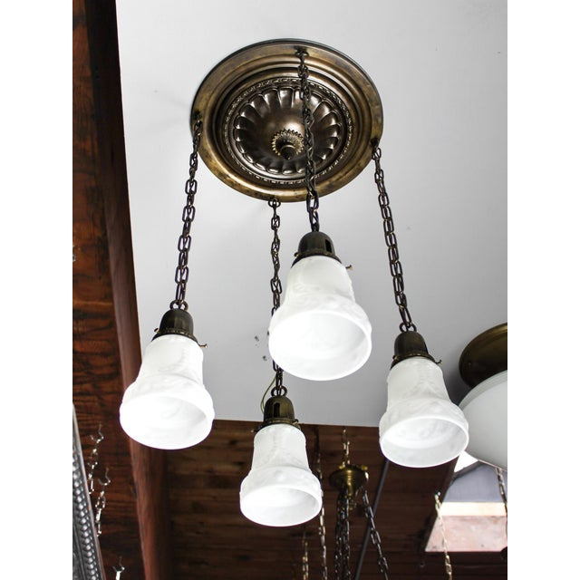Embossed 4-light flush mount fixture with antique finish, all original and fitted with period-correct milk glass shades....