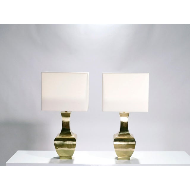 There's a classic beauty to this French 1970s pair of lamps. Their brass structure has the fluid, dramatic curves of...