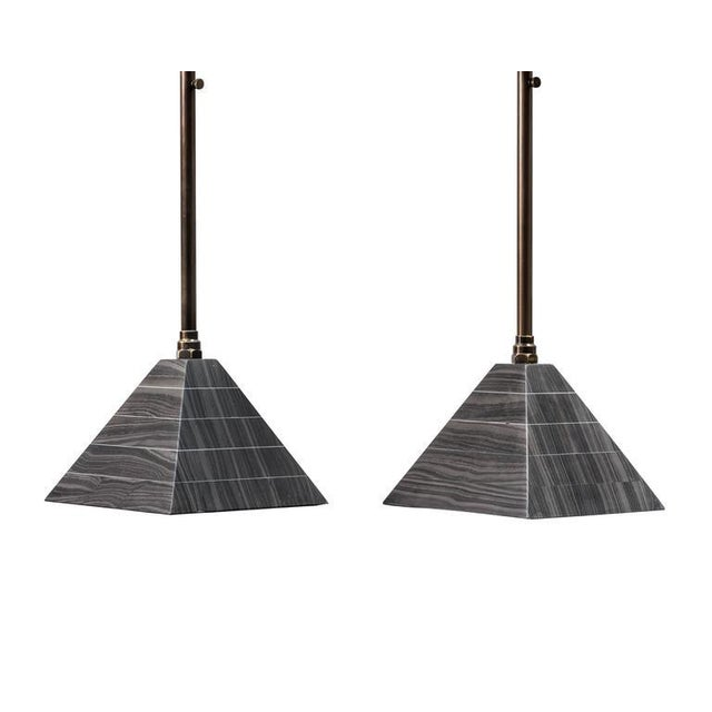 Erickson Aesthetics Marble and Brass Cocktail Tables. Stacked marble pyramid base supports telescoping brass post with...