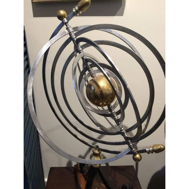 Celestial armillary with a brass centre sun and nine chrome orbital rings that move or lay flat. Mounted on a black iron...