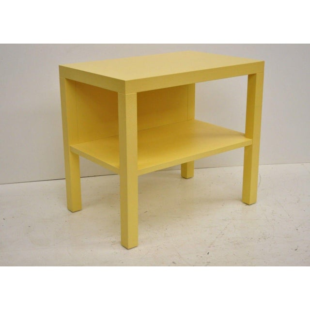 Pair of Decca yellow grasscloth raffia wrapped bedside end tables. Item features yellow raffia wrapped frame, two tiers,...