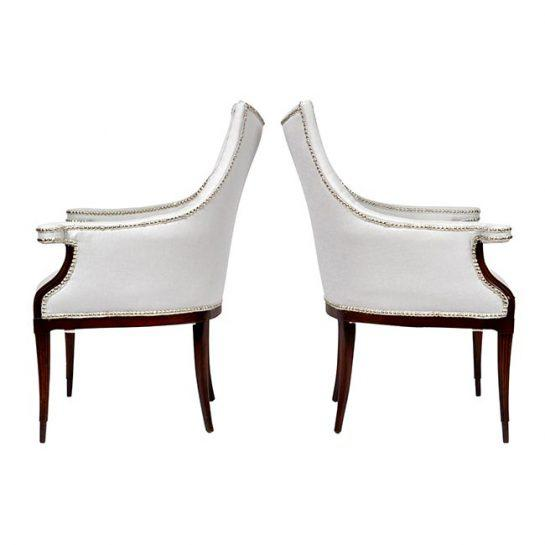 Early 20th century Pair of French Art Deco club chairs. Cuban mahogany frames with tapered fluted legs, scrolled arms,...