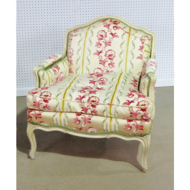Companion pair of Louis XV style chairs. One bergere and one arm chair with distressed paint and textured upholstery.