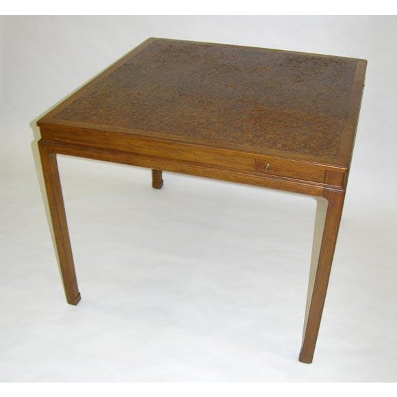 A square game table with a top comprised of nine square cork tiles set in a mahogany frame and pivoting cork lined drink...