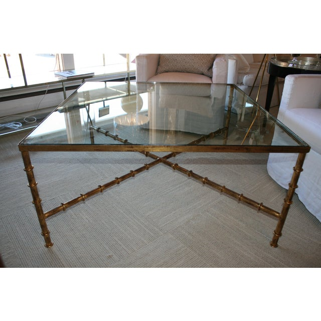 """Amazing faux bamboo x stretcher based coffee table with glass top. Thick, 3/4 """" glass and aged gold finish."""