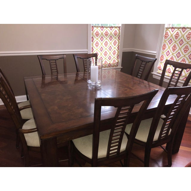 Beautiful square dining room table with a burl and cherry veneer parquet top and 8 matching spindle back chairs (2 with...
