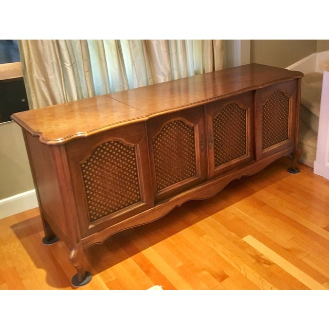 This credenza has storage in the center cabinet, and houses a vintage Garrard 4-speed record player and Clairtone stereo...